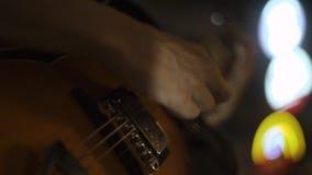 Músico que joga a música em cordas da guitarra no concerto Feche acima da melodia dos jogos do guitarrista à guitarra na fase do  vídeos de arquivo