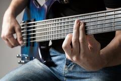 Músico que joga na guitarra-baixo da seis-corda Fotos de Stock