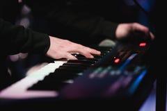 Músico que joga nas chaves do piano do sintetizador do teclado O músico joga um instrumento musical na fase do concerto fotos de stock royalty free