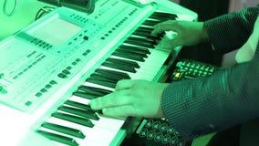 Músico que joga nas chaves do piano do sintetizador do teclado O músico joga um instrumento musical no partido equipa hsnds filme