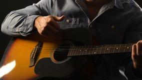 Músico que joga o close up da guitarra acústica, apreciando a sessão viva no desempenho vídeos de arquivo