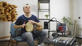 Músico que joga o instrumento do cilindro do djembe no estúdio da música da casa filme