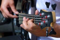 Músico que juega el foco de la guitarra baja en mano izquierda Foto de archivo