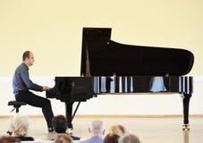 Músico que juega el piano en la academia, Lituania Foto de archivo