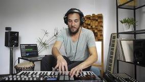 Músico que juega el teclado de Midi en el estudio casero de la música metrajes