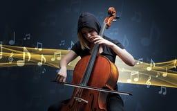 Músico que juega en el violoncelo con las notas alrededor Foto de archivo libre de regalías