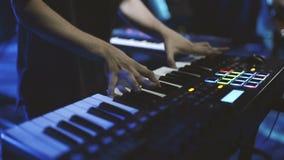 Músico que juega en las llaves del piano del sintetizador del teclado El músico toca un instrumento musical en la etapa del conci almacen de metraje de vídeo