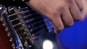 Músico que juega melodía de la guitarra eléctrica Detalles de las secuencias y mano derecha cerca de las recogidas metrajes
