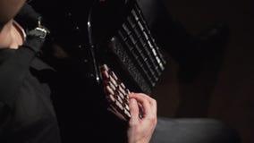 Músico que lleva un sombrero que juega el acordeón en el cuarto oscuro almacen de metraje de vídeo