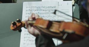 Músico que toca el violín durante un ensayo de la música clásica antes de un concierto almacen de video