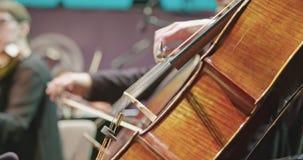 Músico que toca el violoncelo durante un ensayo de la música clásica antes de un concierto almacen de video