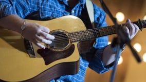 Músico que toca la guitarra acústica en etapa Imágenes de archivo libres de regalías