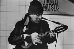 Músico que toca la guitarra dentro del subterráneo en Jackson Heights Foto de archivo