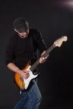 Músico que toca la guitarra eléctrica en fondo oscuro Imágenes de archivo libres de regalías
