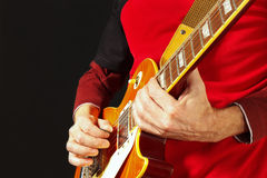 Músico que toca la guitarra eléctrica en fondo oscuro Fotos de archivo