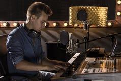 Músico que trabaja y que produce música en su estudio moderno de los sonidos Imagenes de archivo