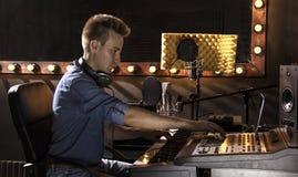 Músico que trabaja y que produce música en su estudio moderno de los sonidos Fotos de archivo libres de regalías