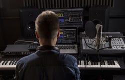 Músico que trabaja y que produce música en su estudio moderno de los sonidos Imágenes de archivo libres de regalías