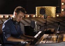 Músico que trabaja y que produce música en su estudio moderno de los sonidos Foto de archivo