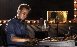 Músico que trabaja y que produce música en su estudio moderno de los sonidos Fotos de archivo