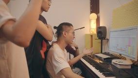 Músicos asiáticos jovenes que trabajan junta corrigiendo la música metrajes