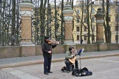 Músicos da rua de Rússia, St Petersburg que jogam instrumentos musicais no fundo da estrutura do jardim do verão Imagem de Stock Royalty Free