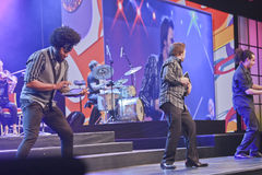 Músicos de la banda de rock que juegan en iPads Foto de archivo