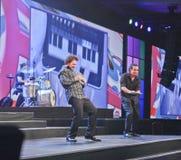 Músicos de la banda de rock que juegan en iPads Imagen de archivo libre de regalías