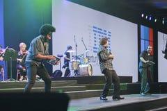 Músicos de la banda de rock que juegan en iPads Fotografía de archivo libre de regalías