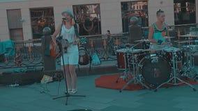 Músicos de la calle, muchacha que toca la guitarra y que canta, individuo que juega los tambores metrajes