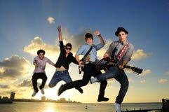 Músicos de sexo masculino jovenes que saltan con los instrumentos Fotos de archivo libres de regalías