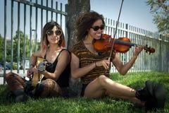 Músicos fêmeas assentados sob uma árvore que joga instrumentos Fotos de Stock