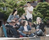 Músicos felices de los adolescentes en parque Fotos de archivo