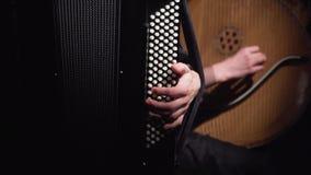 Músicos muchacha y muchacho en un cuarto oscuro que juega en el acordeón y el bandura almacen de metraje de vídeo