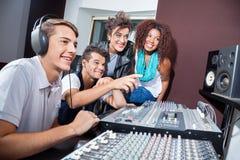 Músicos multiétnicos que mezclan el audio junto en la tabla imagen de archivo