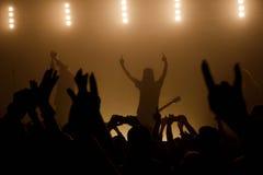 Músicos que aumentan para arriba las manos con la muchedumbre en primero plano Fotos de archivo