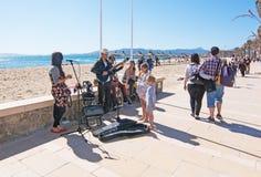 Músicos que juegan por la playa Imagen de archivo