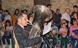 Músicos que se realizan y que marchan a lo largo de nazarenes en un desfile en la procesión de Domingo de Ramos imagen de archivo