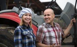 Mûrissez et des jeunes exploitants agricoles posant avec de vieux agrimotors dans le bétail Photographie stock libre de droits