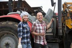 Mûrissez et des jeunes exploitants agricoles posant avec de vieux agrimotors dans le bétail Photo stock