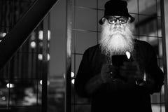 Mûrissez l'homme barbu semblant méfiant tout en à l'aide du téléphone dans noir et blanc photos stock