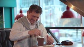 Mûrissez l'homme bel dans une chemise blanche avec du sucre de sourire d'émois de chandail avec un bâton dans le café nouvellemen banque de vidéos
