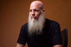 Mûrissez l'homme chauve avec la longue barbe grise sur le fond brun photographie stock