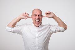 Mûrissez l'homme européen fermant ses oreilles en raison du bruit et du bruit forts Je ne veux pas écoute vous photos libres de droits