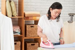 Mûrissez la femme faisant la blanchisserie photo libre de droits