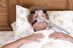 Mûrissez la machine aînée d'Apnea de sommeil de la femme CPAP images stock