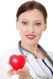 Mûrissez le docteur féminin avec le coeur dans sa main. Photographie stock