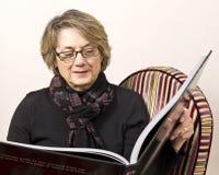 Mûrissez le femme affichant le grand livre Image stock