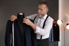 Mûrissez le tailleur prenant des mesures de veste photos stock