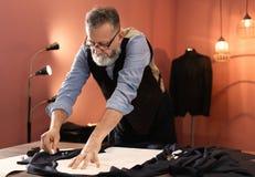 Mûrissez le tailleur travaillant avec le modèle de couture image stock